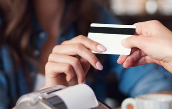 Una mujer paga un café con tarjeta de crédito