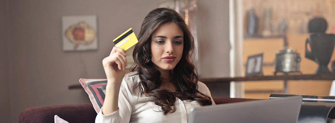 Una mujer sostiene su tarjeta de crédito frente al ordenador