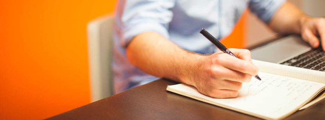 Hombre con un ordenador tomando notas en un cuaderno