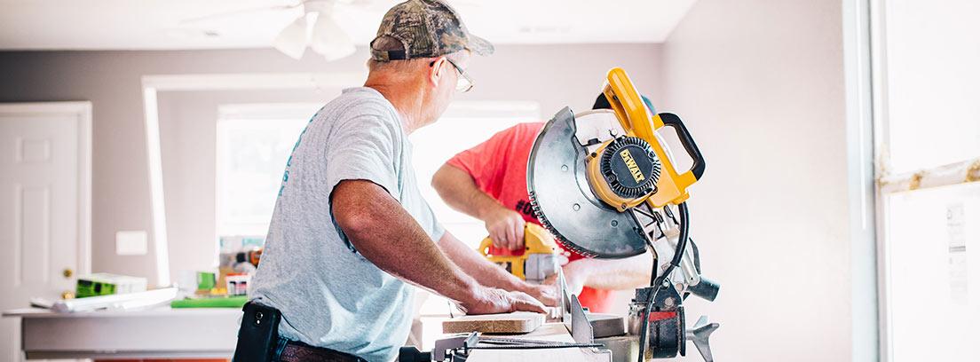 Hombre con gafas y gorra trabaja sobre tablón de madera junto a otros operarios