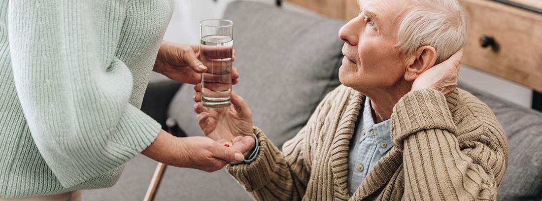 Anciano sentado en un sofá recibiendo un vaso de agua