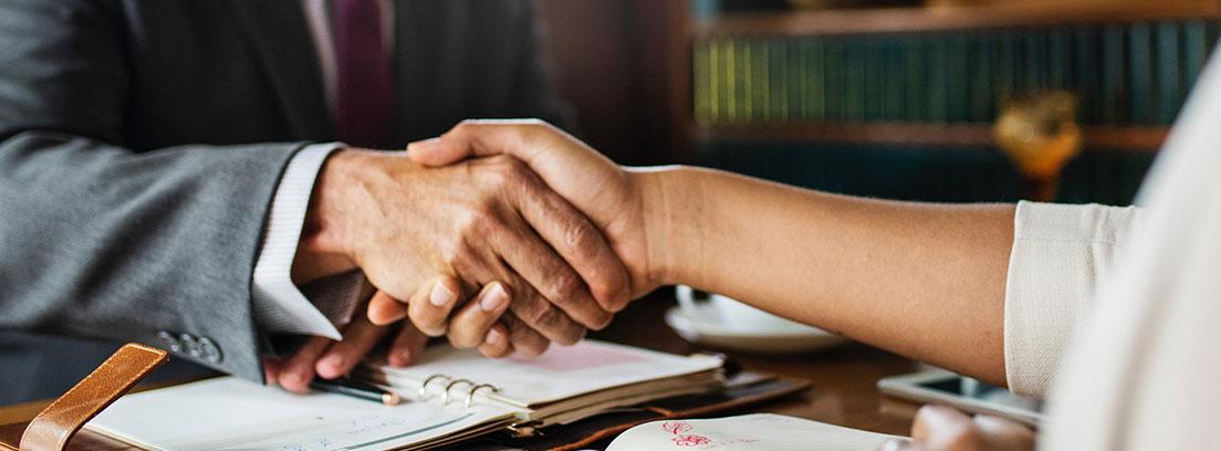 Hombre y mujer estrechando las manos sobre una mesa con libros abiertos