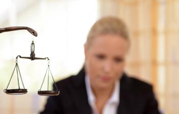 Estatua de la justicia en un despacho y mujer con traje escribiendo
