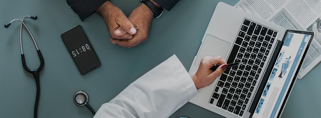 Vista cenital de un médico junto a su paciente en una mesa con un ordenados y utensilios médicos