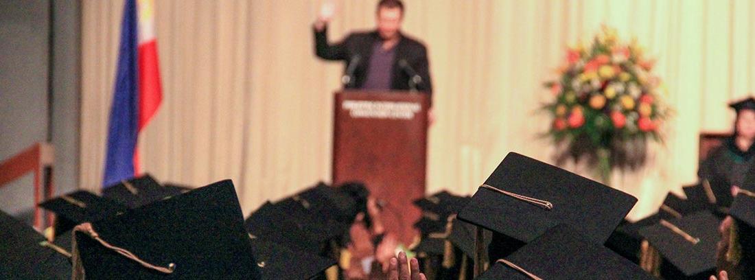 Personas con birretes y togas frente a un escenario con atril y persona hablando