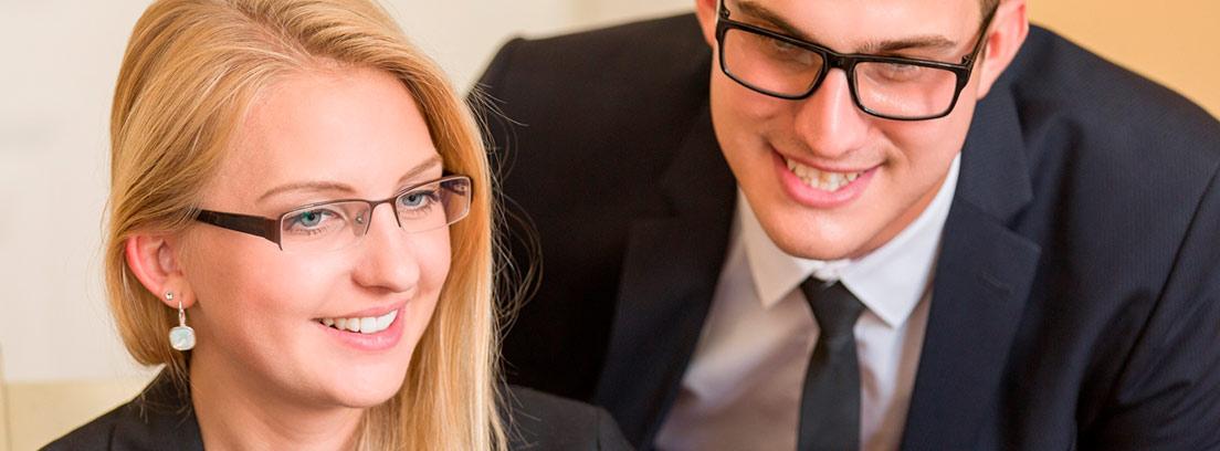 Hombre y mujer jóvenes mirando la pantalla de un ordenador