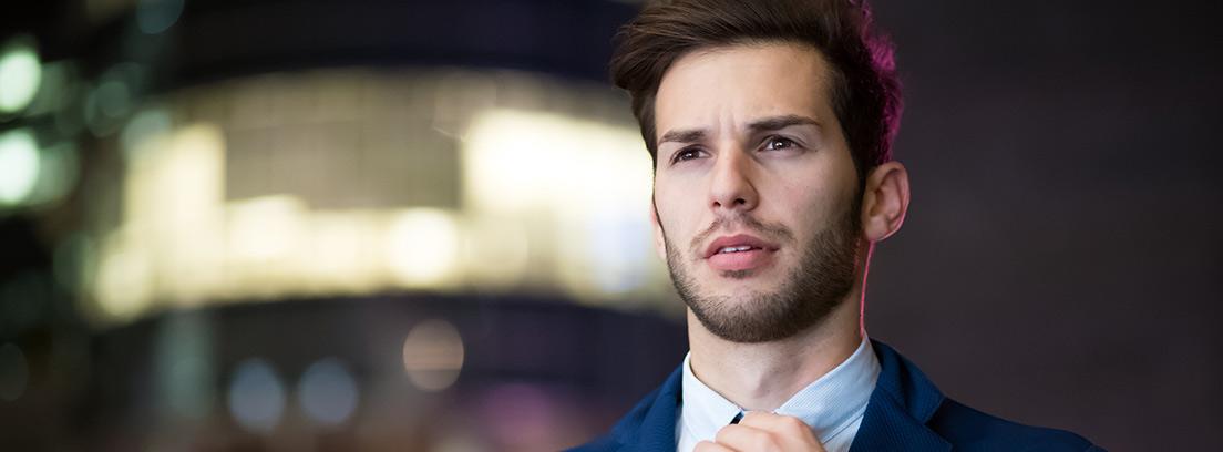 Hombre joven con traje ajustándose la corbata