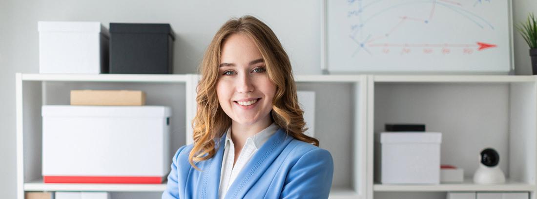 Mujer joven con traje azul cruzada de brazos y con gesto sonriente