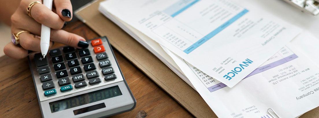Mano sobre calculadora con varias facturas