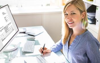 Mujer sonriente con calculadora frente a un ordenador