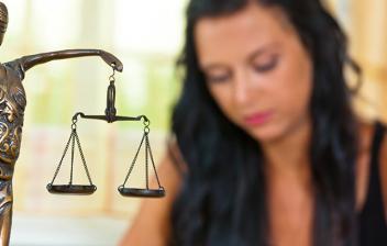 Mujer sentada en una mesa con una figura de una mujer con balanza