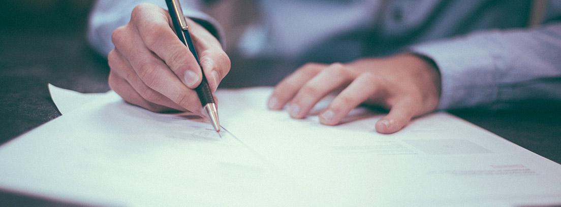 Manos con bolígrafo escribiendo sobre hojas