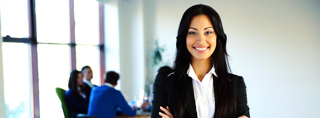 Mujer sonriente y con los brazos cruzados delante de un grupo de personas sentadas alrededor de una mesa