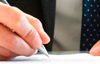 Mano con boli escribiendo en un papel