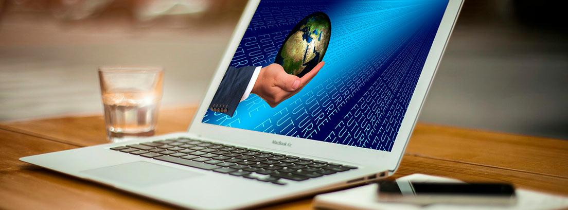 Ordenador con una mano sujetando la bola del mundo en la pantalla
