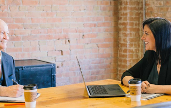 Un hombre y una mujer hablan en una sala de oficina