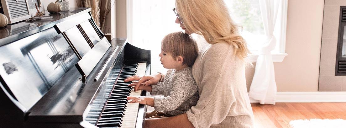 Madre con niño sobre sus rodillas sentados al piano