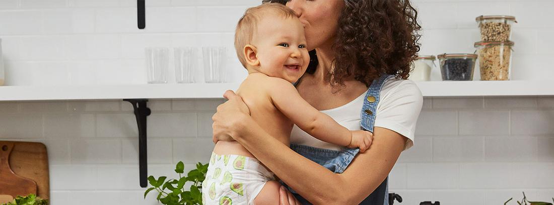 Mujer besando a un niño con pañal que sostiene en brazos