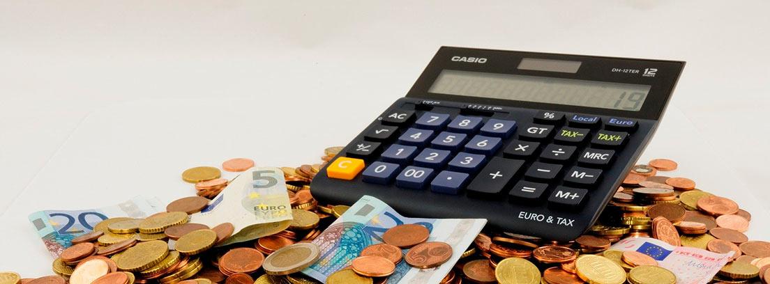 Calculadora sobre un montón de monedas y billetes