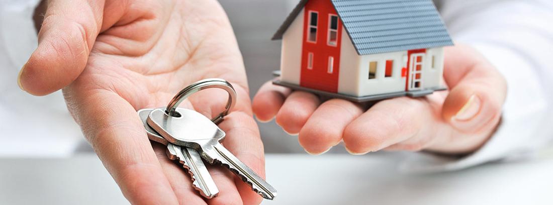 Una mano sujetando una llave y otra, una casa