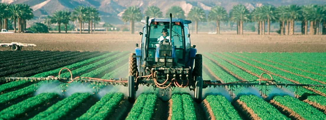 Tractor regando un campo cultivado