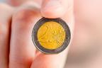Mano sujetando una moneda de dos euros