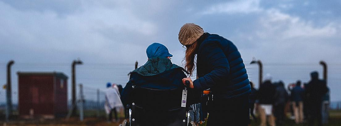 Persona de espaldas en silla de ruedas junto a otra persona de pie