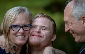 Mujer abraza a chico con síndrome de Down y otro hombre les mira