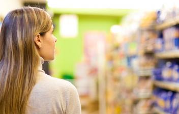 Mujer de espaldas con un carro de la compra en un supermercado