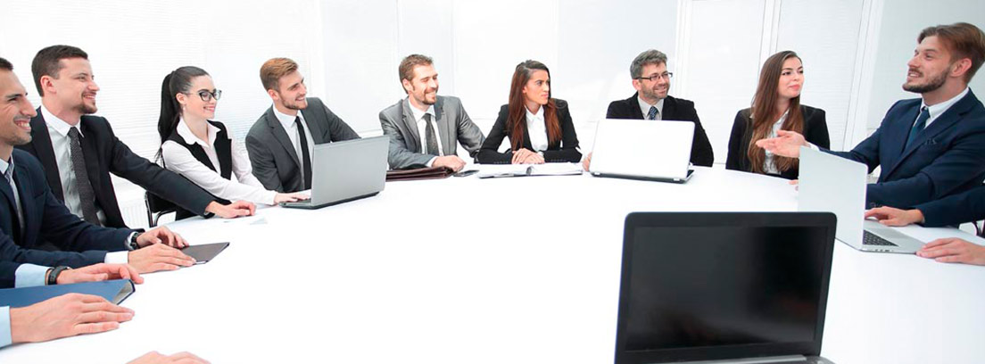 Hombres y mujeres en torno a una meda redonda y con ordenadores