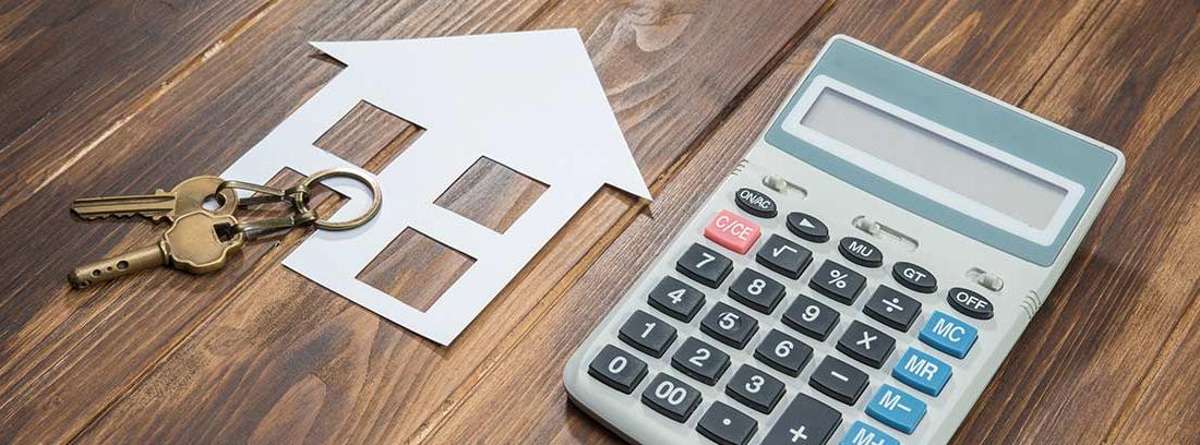 Calculadora junto a unas llaves y el relieve de una casa