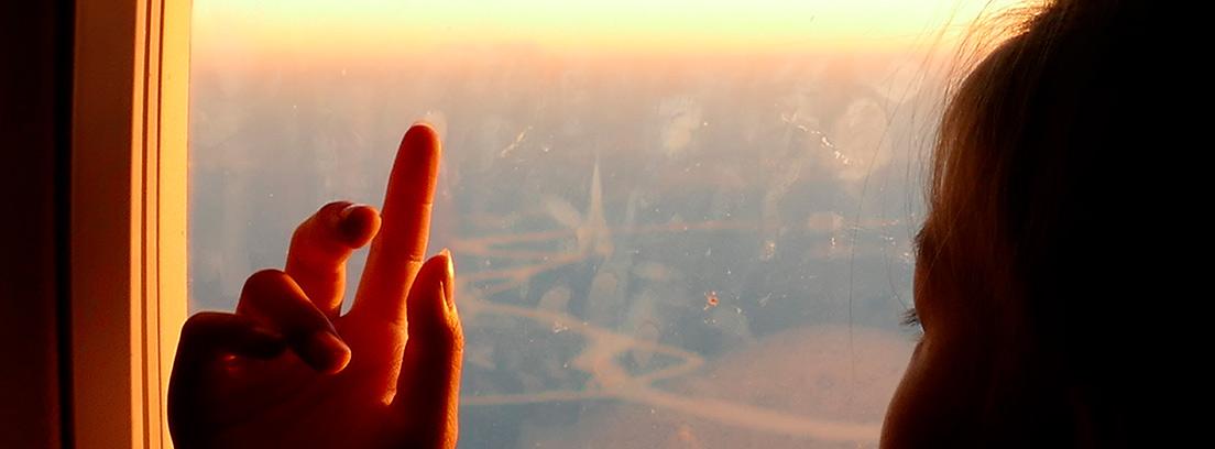 Silueta de una niña mirando por la ventana de un avión