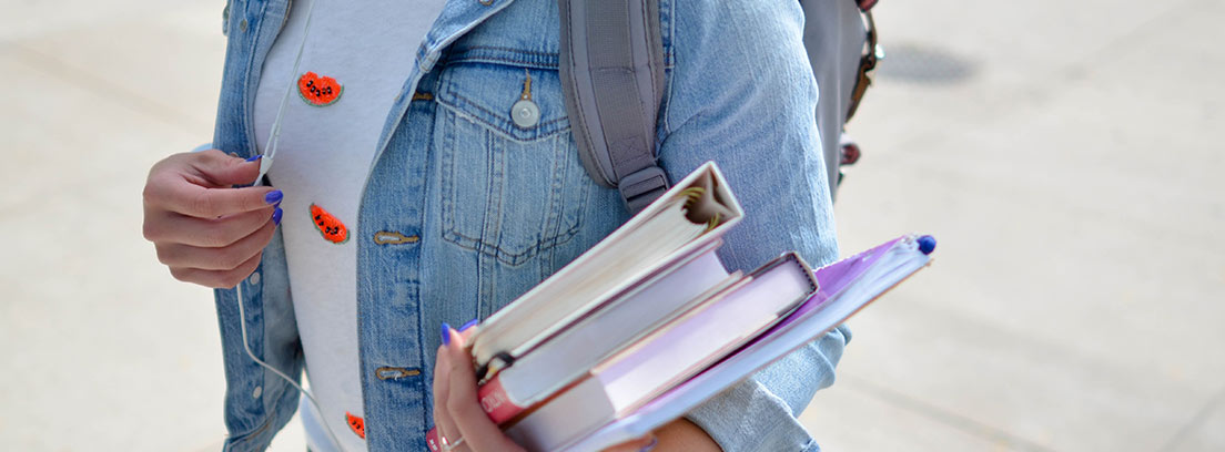 Persona con varios libros en la mano, cascos y mochila en la espalda