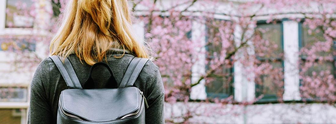 Mujer con mochila negra de espaldas frente a un edificio en la calle