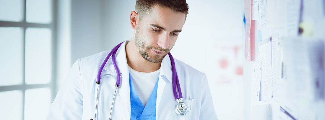 Médico con bata y fonendo revisando un informe