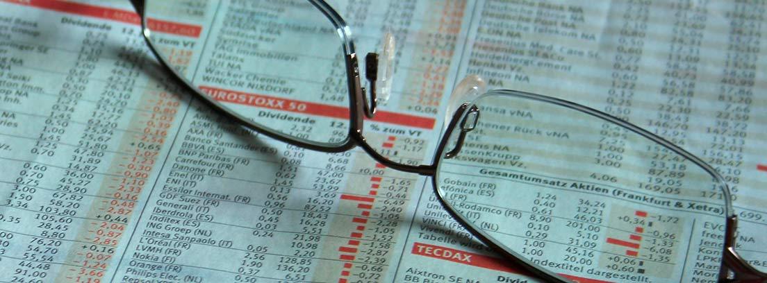 Gafas sobre un periódico con valores de bolsa