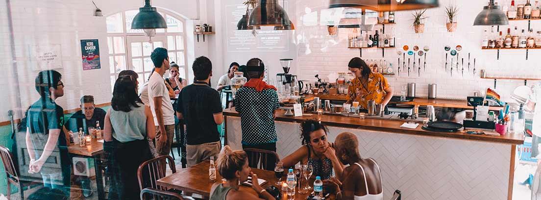 Barra de bar con personas esperando y mesas con gente sentadas