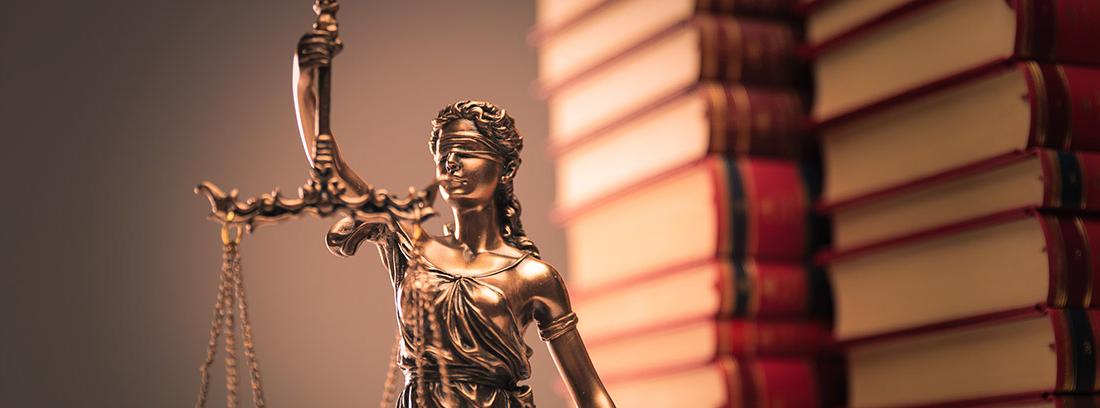 Figura de la Justicia frente a una pila de libros