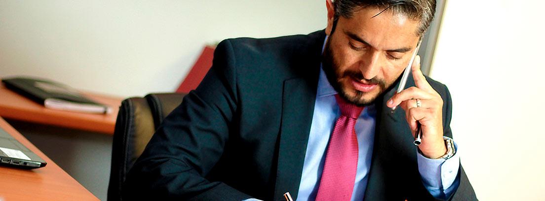 Hombre con traje escribiendo y hablando por teléfono