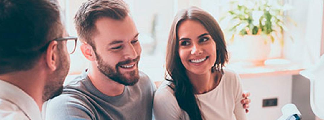 Mujer y hombre miran hacia otro hombre que les muestra una carpeta