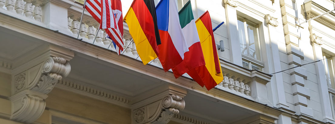 Banderas de distintos países colgando del balcón de un consulado