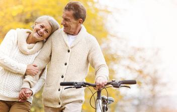 Hombre y mujer mayores con una bici paseando por un paisaje otoñal