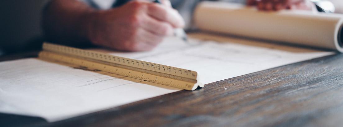 Manos con lápiz sobre planos y junto a escalímetro