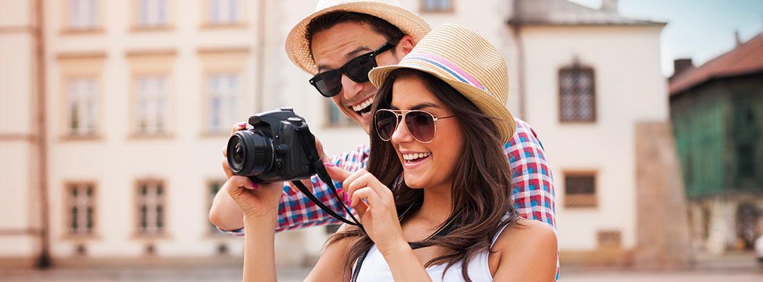 Una pareja de turistas observa las fotografías en su cámara