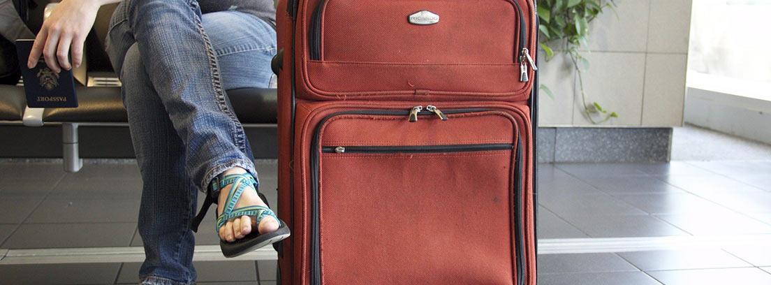 Mujer sentada junto a su maleta sosteniendo un pasaporte