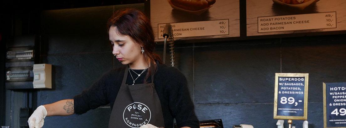 Mujer con delantal negro y guantes blancos detrás de una barra con comida