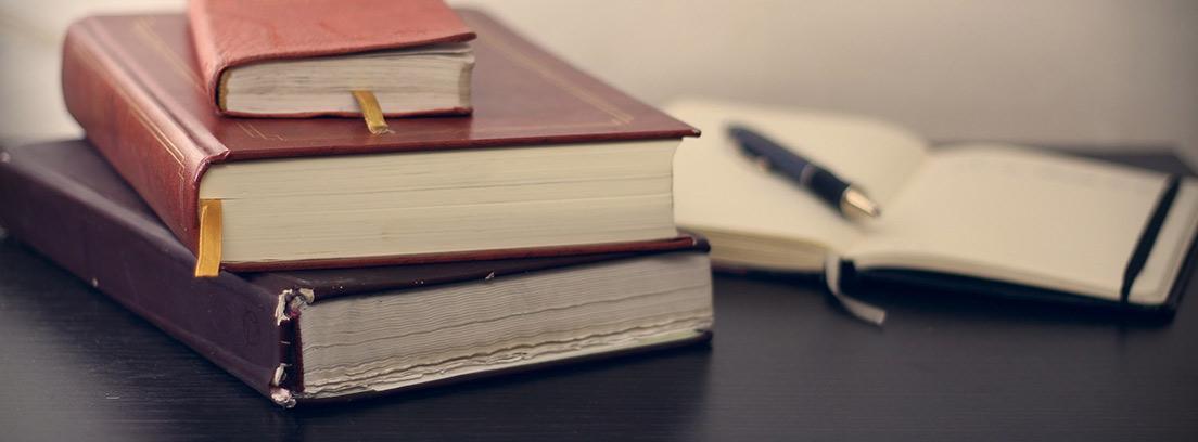 Tres libros apilados junto a un libro abierto con un bolígrafo
