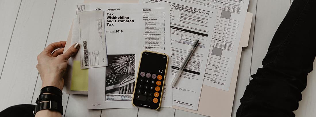 Mano sujeta facturas y formularios junto a calculadora y bolígrafo