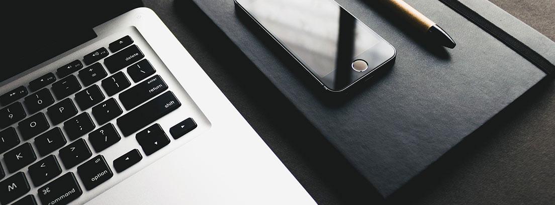 Agenda y móvil junto a un ordenador