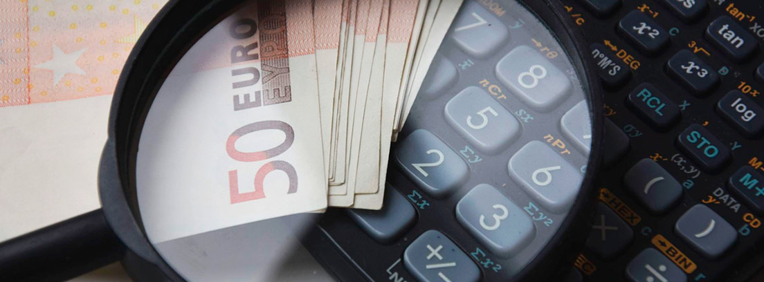 Lupa sobre billetes de 50 euros y una calculadora